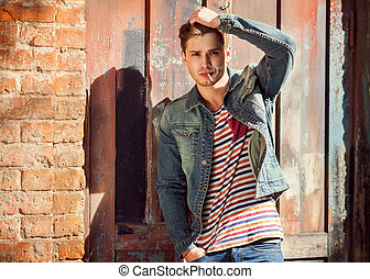 Hipster style guy Fashion man standing near a wooden door