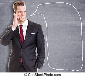 Businessman talking on the phone in front of a blackboard with l