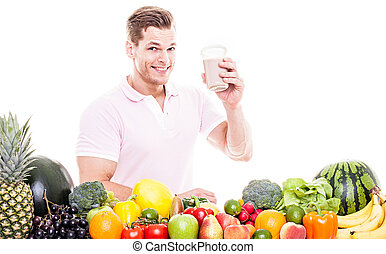 Athletic man drinking a protein shake behind a table full of...