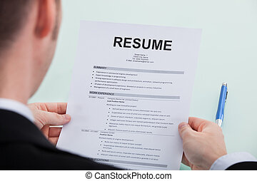 Businessman Reading Resume At Office Desk - Cropped image of...