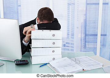 Stressed Businessman Resting Head On Binders At Desk -...