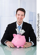 Businessman Holding Piggybank At Desk