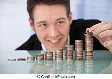 Happy Businessman Stacking Coins In Increasing Order - Happy...