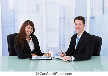 Business People Discussing Over Graphs At Desk