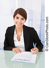 Smiling Businesswoman Signing Contract At Desk - Portrait of...