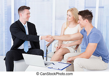 Young Couple Shaking Hands With Financial Consultant - Young...