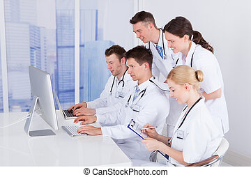Doctors Working Together On Computer In Hospital