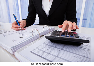 Businesswoman Calculating Tax - Midsection of businesswoman...