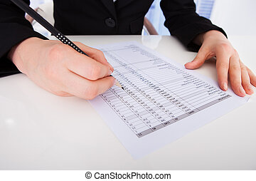 Businesswoman Writing On Financial Paper - Cropped image of...