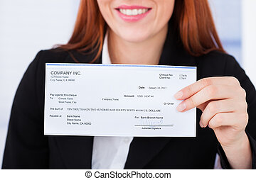Smiling Businesswoman Holding Cheque - Midsection of smiling...