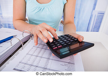 Woman Calculating Home Finances At Desk - Midsection of...