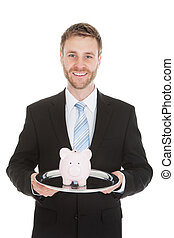 Businessman With Piggybank On Tray - Portrait of mid adult...