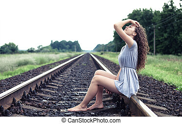 Girl on the railway - The beautiful girl sits on the railway