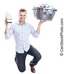 Cheerful young man lifting an electric iron and a basket...