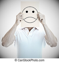 Young man with an unhappy smiley card covering face - Young...
