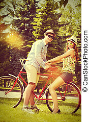 amorous - Happy young couple in summer park rides a bike....