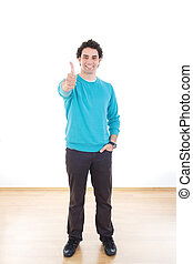Attractive happy young man standing showing thumb