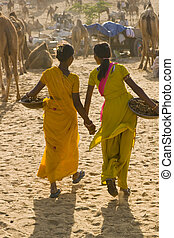 Indian Teens - Teenage Indian girls carrying baskets of...