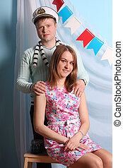 Beautiful smiling woman and man pose in studio with marine decor