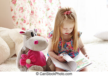 Pretty little blonde girl sits near soft toy on carpet and...