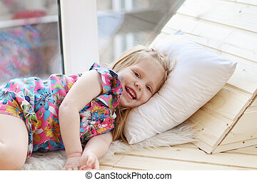 Pretty little blonde girl laughs and lies on white pillow...