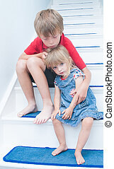 Sad Children - A sad brother and sister sitting on the...
