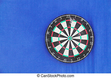 Round dartboard with numbers and with javelins on blue wall
