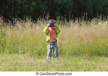 Little pretty girl stands on green grass and shoots at...