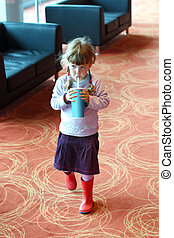 Little girl with pigtails drinking soda from plastic tube