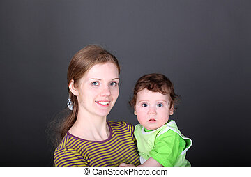 Portrait of happy young mother with cute little son in arms