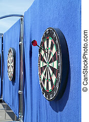 Dartboard with one javelin on blue wall on street in summer...