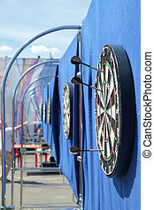 Dartboard with javelins on blue wall on street in summer day