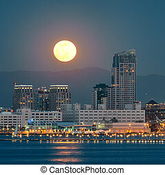 San Diego downtown skyline and full moon over water at night