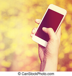 Woman hand holding smartphone against spring green and...