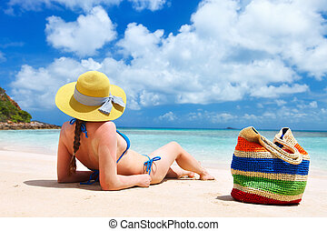 Young woman relaxing at beach - Back view of a young...