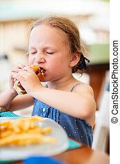 Little girl eating hot dog