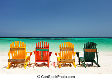 Colorful chairs on Caribbean beach - Row of colorful wooden...