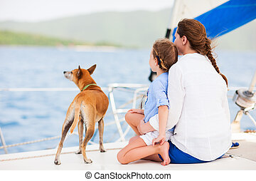 Family sailing on a luxury yacht - Back view of mother,...