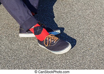 Blue sneakers worn with red and blue plaid socks by a man