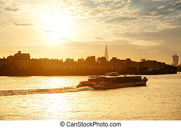 Thames River sunset - A tourism boat in Thames River at...