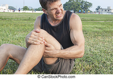 Leg injury - Man suffers painful hamstring injury and holds...
