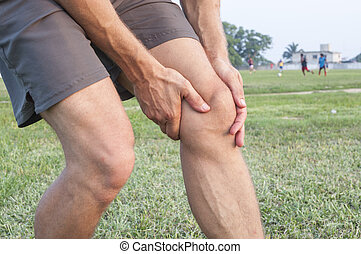 Knee injury - Closeup of athletic Caucasian man holding his...