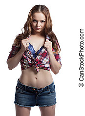 Comely young girl posing unbuttoning her shirt, isolated on...