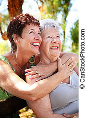 beautiful senior mother and daughter hugging and looking up