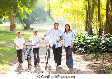 indian family walking outdoors - happy indian family of four...