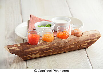 red caviar assorti with herbs and sour cream on wooden plate