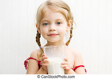 Child drinking milk - Cute little girl drinking a large...