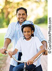 indian father and daughter outdoors on a bike