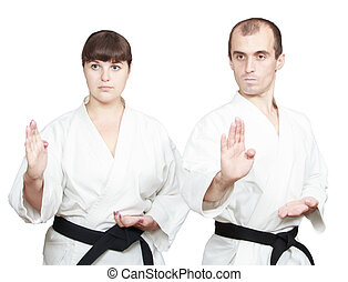 Athletes doing block Shuto-uke - Adult athletes with black...