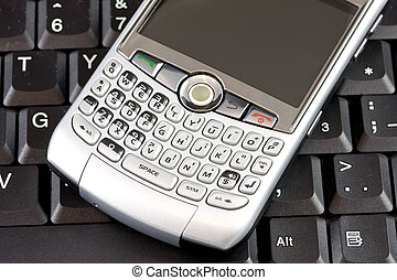 Mobile with laptop background - Closeup of mobile phone with...